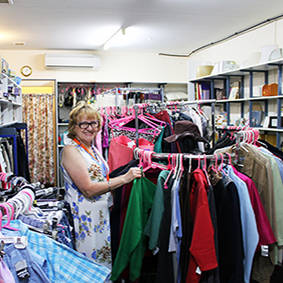 Image of woman volunteer racking clothing inside the Eltham Store
