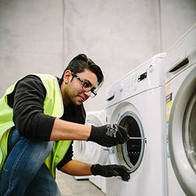 Image of man working on a washing machine