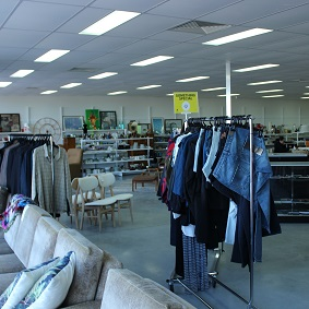 Inside an op shop showing furniture and clothing racks