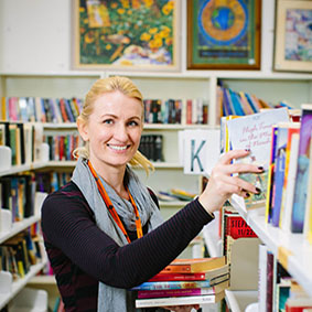 Image of young volunteer stacking bookshelves